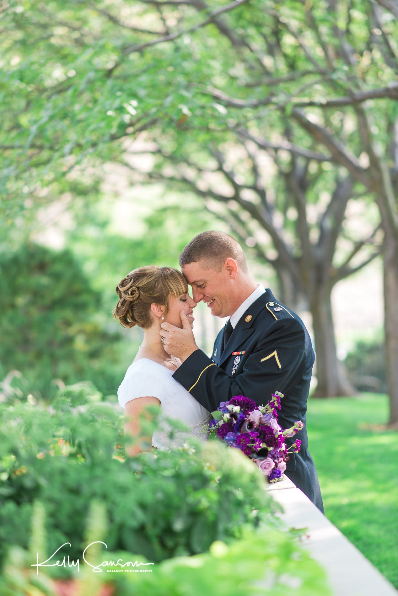 A groom in dress military touches his brides face for wedding photography at the Bountiful LDS temple.