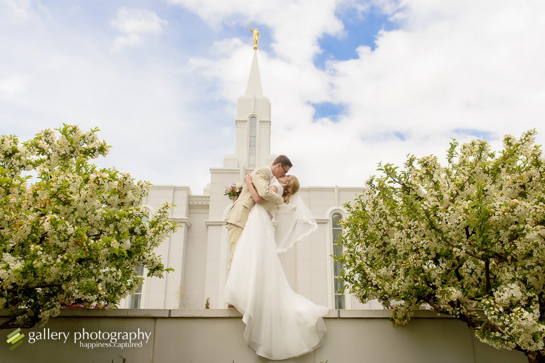 A groom dips his bride and kisses her while standing on a wall in front of the Bountiful LDS temple for wedding photography at the Bountiful LDS temple.