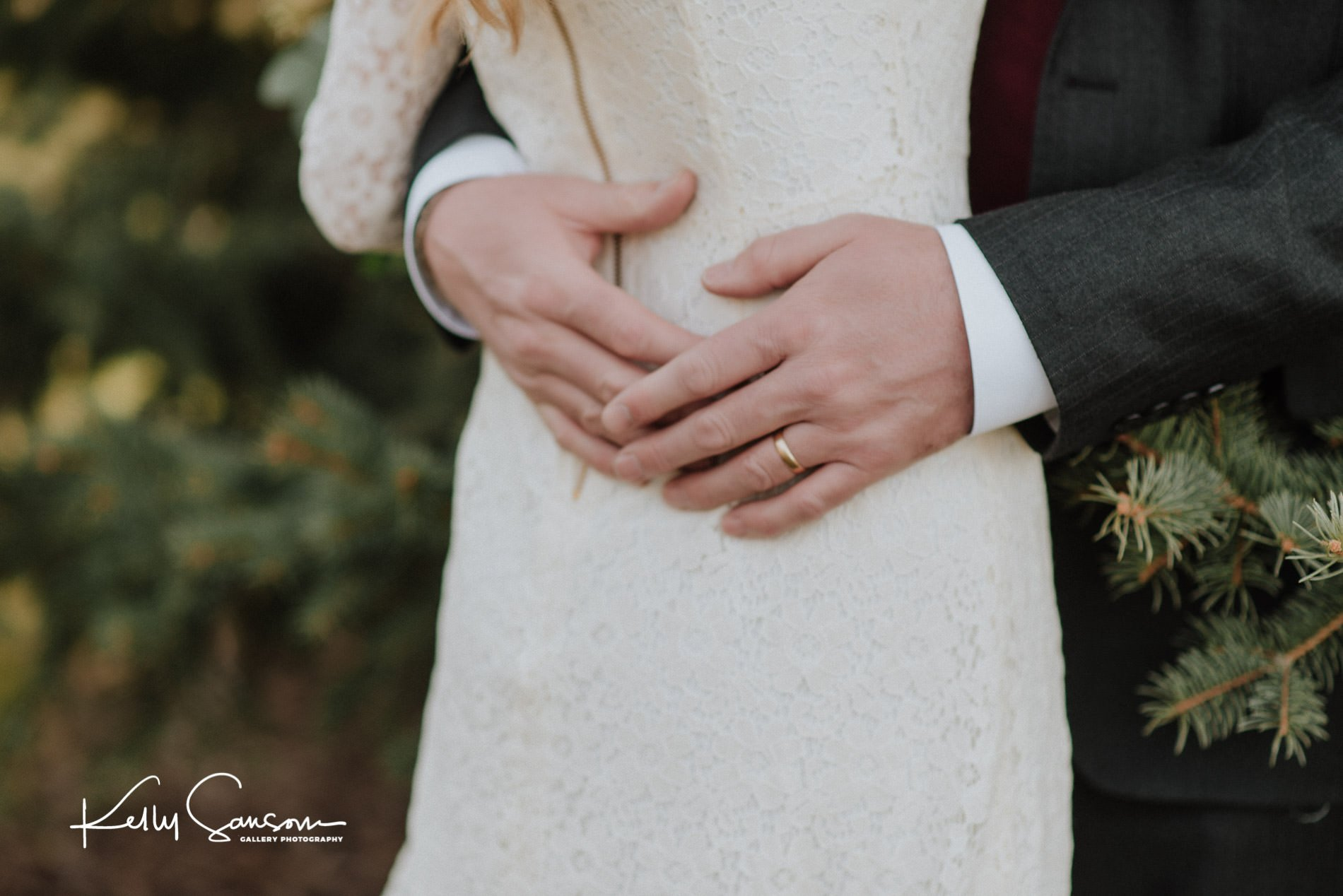 A grooms hands encircle his bride in front of a pine tree for wedding photography at the Bountiful LDS temple.