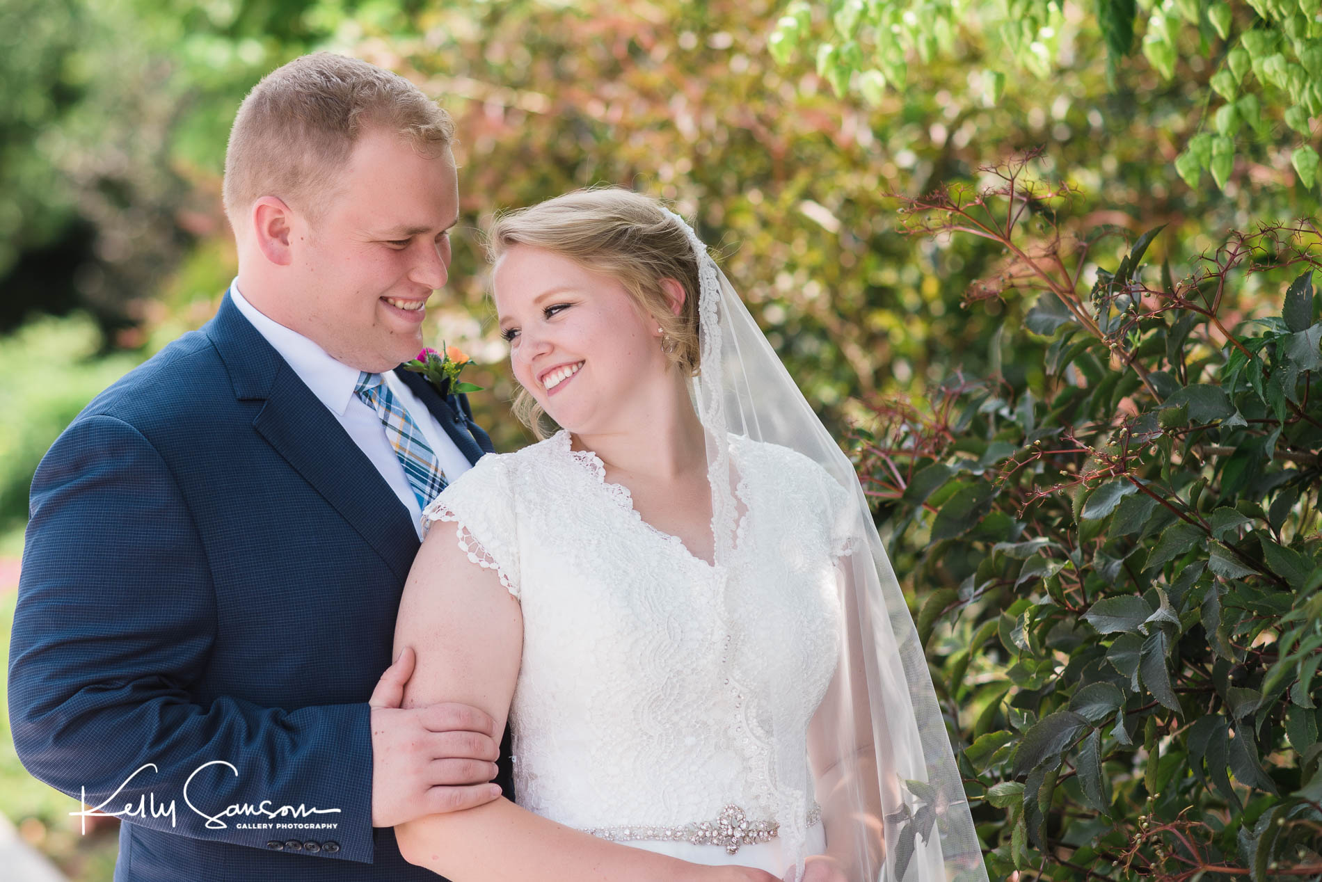 A groom looks at his bride and smiles for Jordan river temple wedding photography.