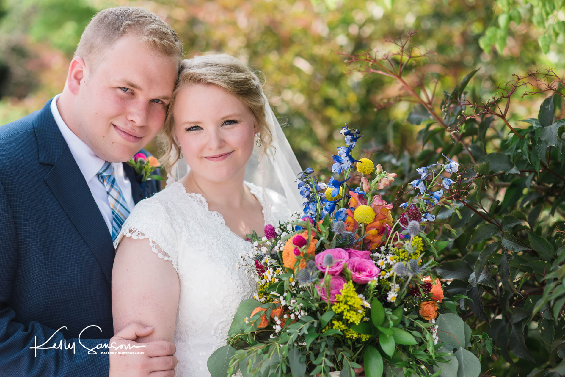 A bride and groom snuggle and look at the camera for Jordan river temple wedding photography.