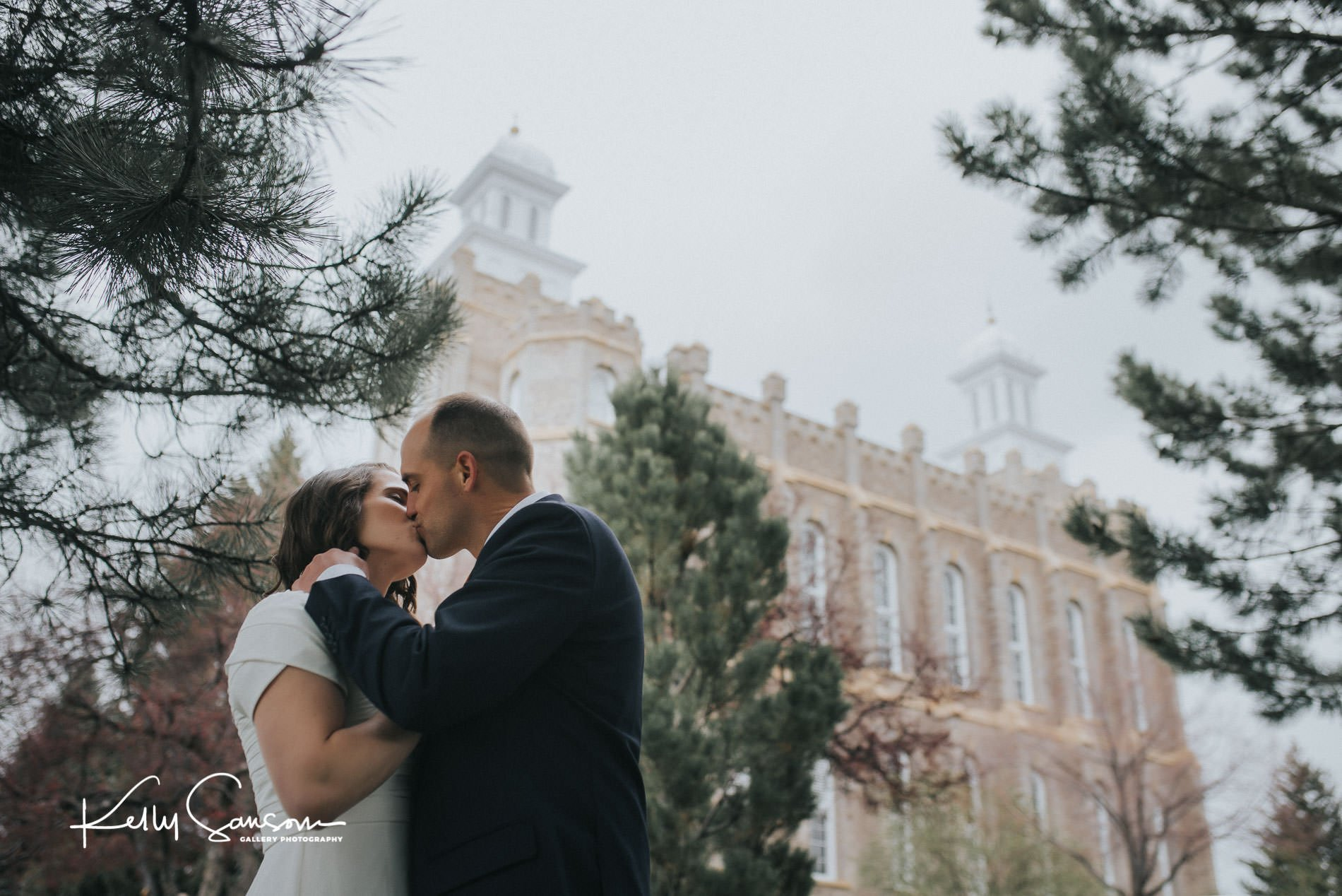 A bride and groom kissing in front of the temple for Logan temple wedding photography.