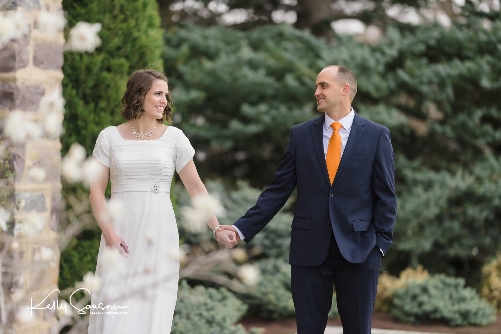 A bride and groom holding hands looking at each other for Logan temple wedding photography.