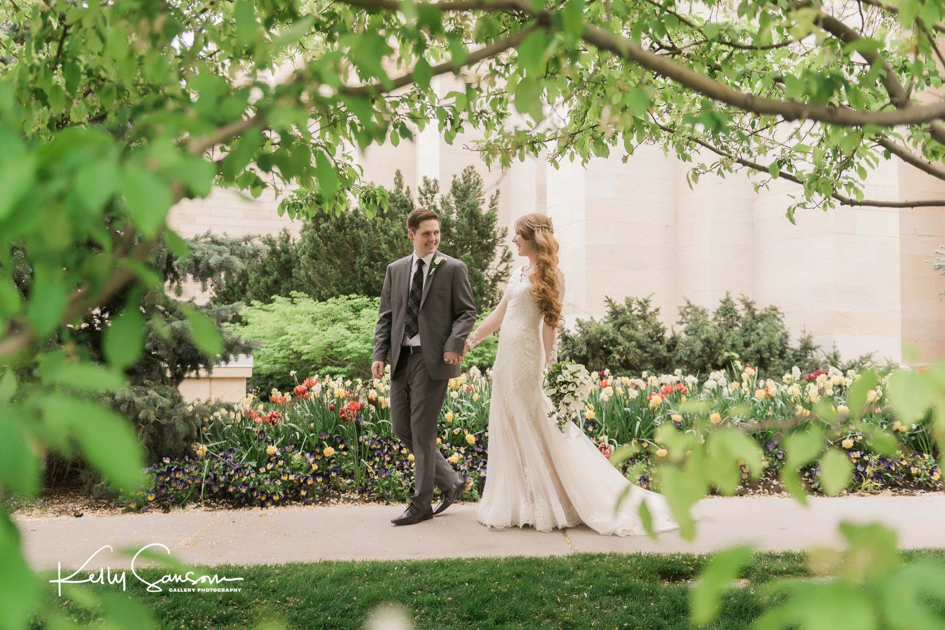 A groom leading his bride by the hand through some trees for Manti temple wedding photography.