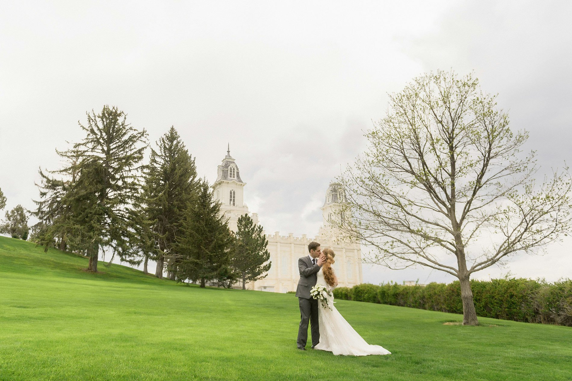 A groom touches his brides face and kisses her for Manti temple wedding photography.