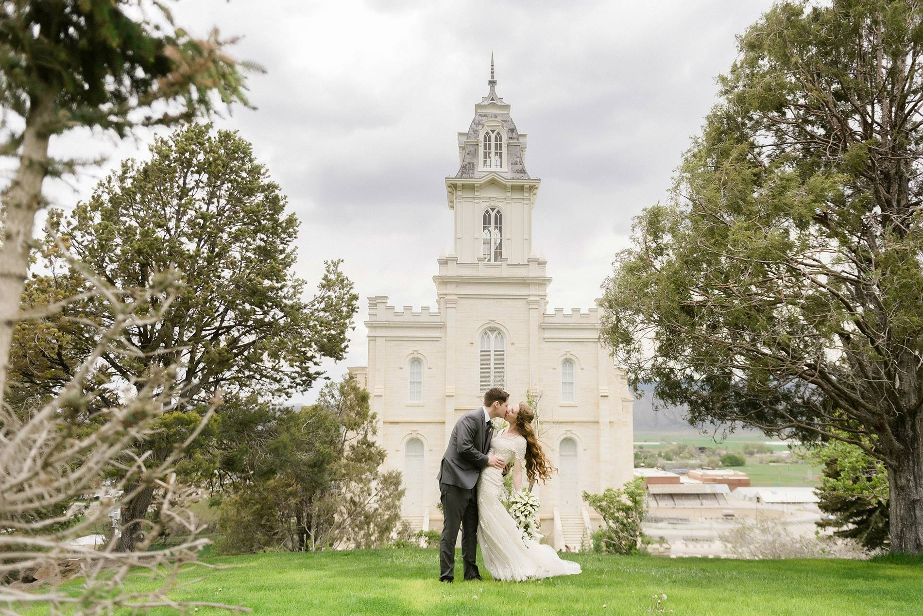 A bride and groom kissing on the East side of the Manti temple for Manti temple wedding photography.