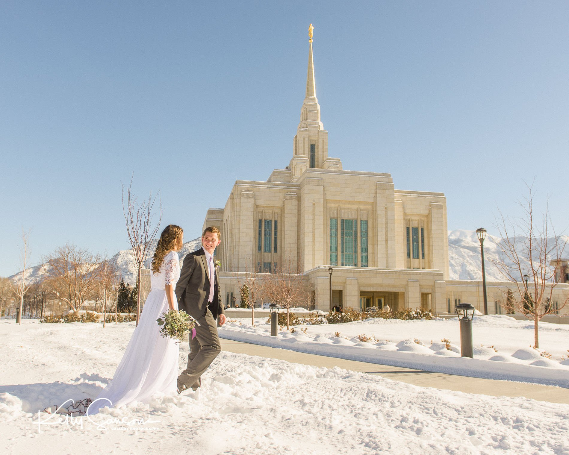A groom leads his bride through the snow for Ogden LDS temple wedding photography.