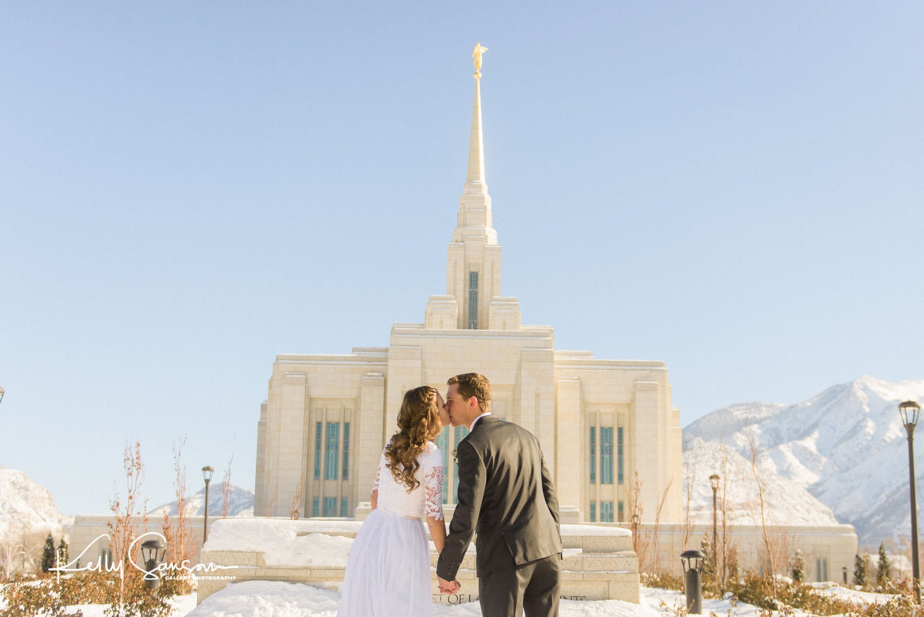 A bride and groom lean together to kiss with the backs to us for Ogden LDS temple wedding photography.