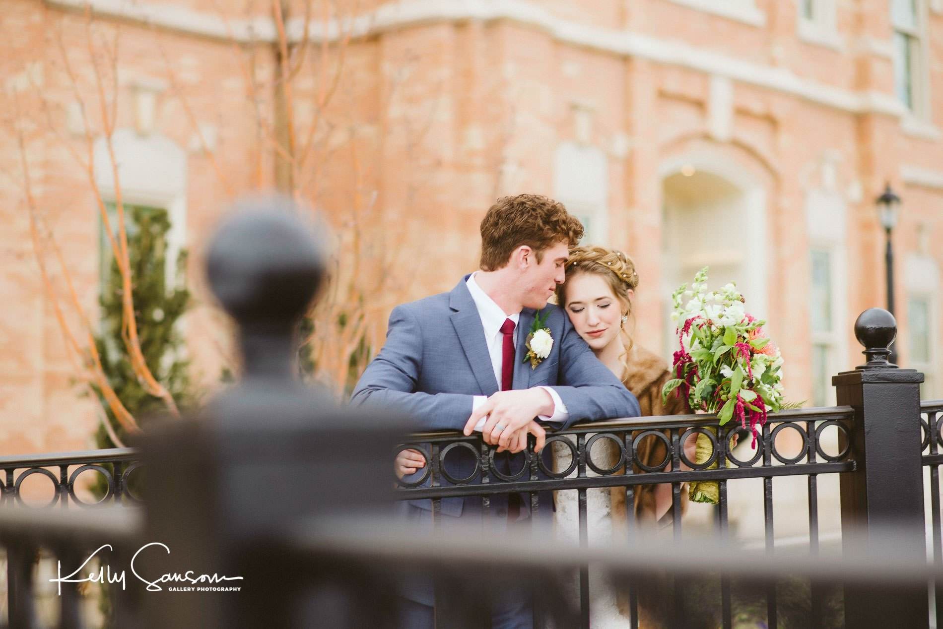 Groom looking at bride while leaning on railing for wedding photography at the provo city center lds temple.