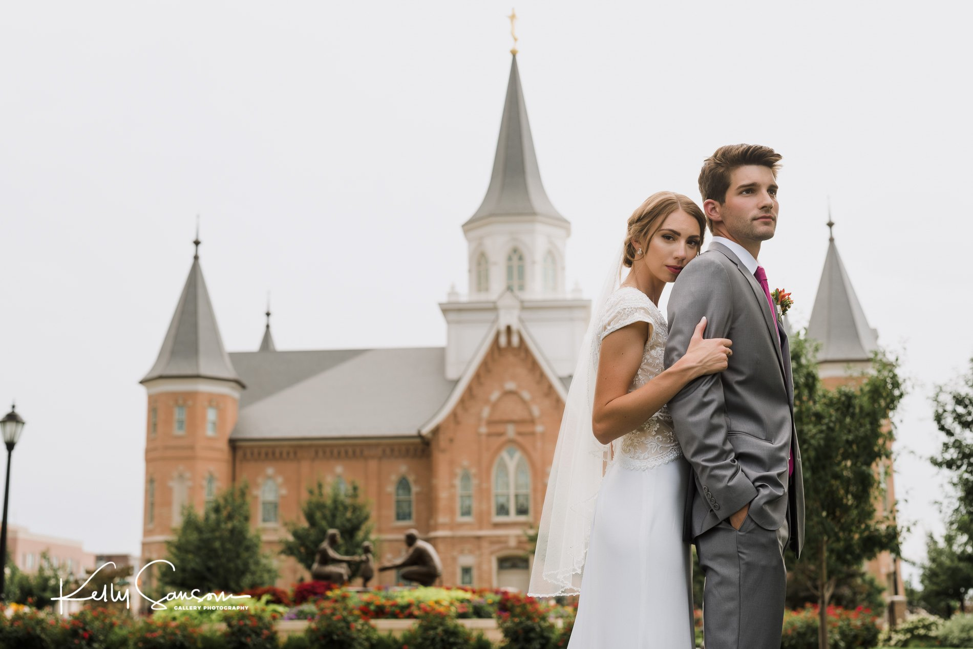 Bride snuggling into the back of the groom for wedding photography in front of provo city center lds temple.