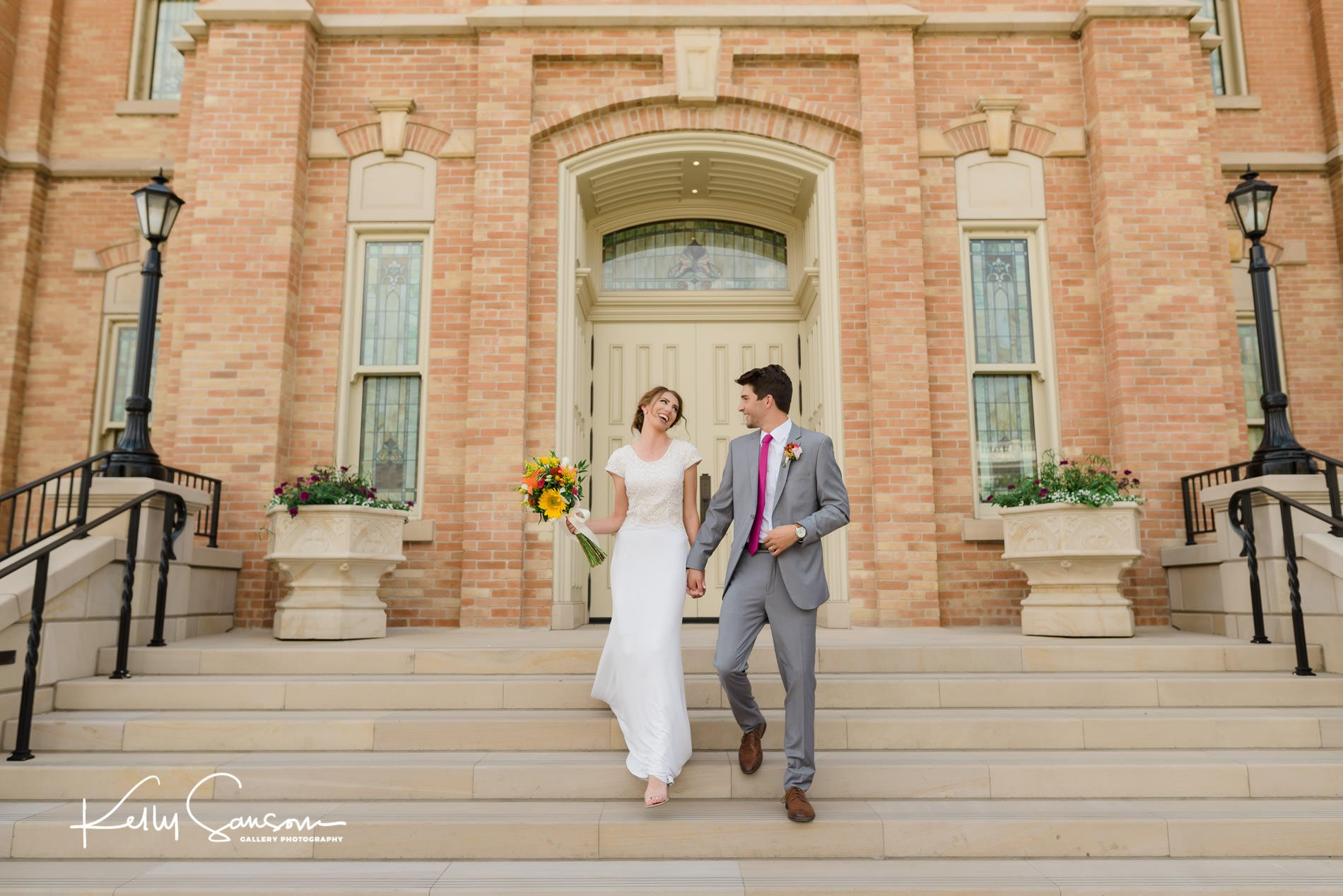 Bride and groom walking down the stairs holding hands in front of the provo city center lds temple.
