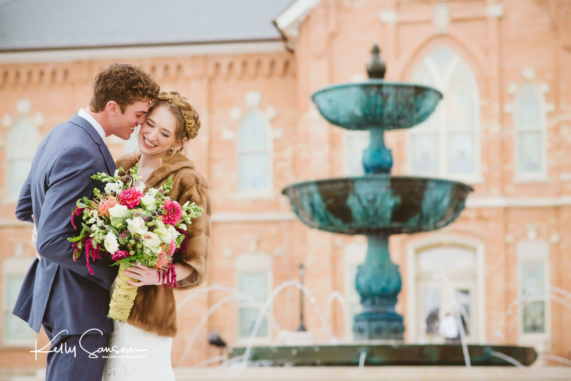 Bride and groom snuggling in front of fountain for wedding photography at Provo city center lds temple.