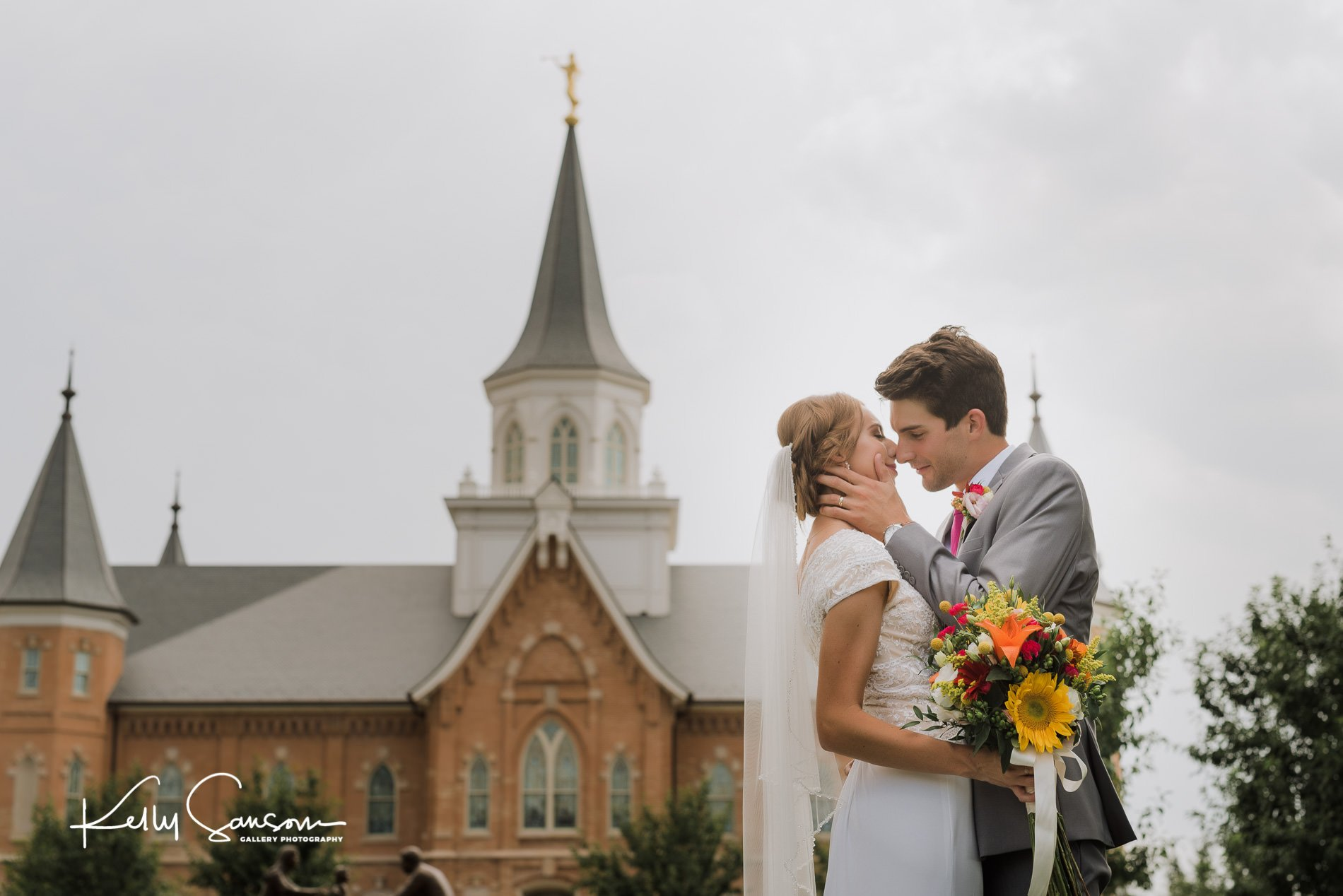 Groom going in for a kiss with his bride for wedding photography at the provo city center lds temple.